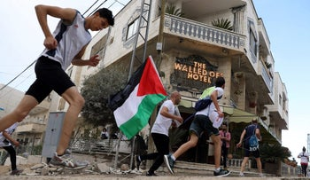 Participants run past Banksy's Walled Off Hotel during the annual Palestine Marathon in Bethlehem, March 31, 2017.