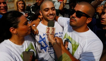 Elor Azaria, smiling in the center of the picture wearing a white T-shirt with blue writing, being embraced by supporter wearing a white T-shirt with Azaria's picture on it. A Channel 2 TV correspondent who we cannot see is holding a mic to Azaria's face.