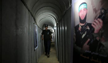 In this Wednesday, July 20, 2016 file photo, a Palestinian youth walks inside a tunnel used for military exercises during a weapon exhibition at a Hamas-run youth summer camp, in Gaza City.