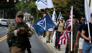 White supremacists pass a militia member as the they arrive for a rally in Charlottesville, Virginia, August 12, 2017.