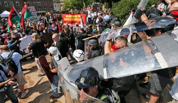 White nationalist demonstrators use shields as they clash with counter demonstrators at the entrance to Lee Park in Charlottesville, Virginia, August 12, 2017.
