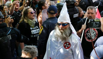 Members of the KKK escorted by police past a large group of protesters during a rally in Charlottesville, Va, July 8, 2017.