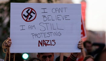 """A demonstrator holds signs during a rally in response to the Charlottesville, Virginia car attack on counter-protesters after the """"Unite the Right"""" rally organized by white nationalists, in Oakland, California, U.S., August 12, 2017. Picture taken August 12, 2017. REUTERS/Stephen Lam"""