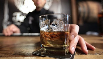 Bartender Chisei Kawaguchi places a glass of Jack Daniel's whiskey on a coaster for an arranged photograph during a media preview of the Jack Daniel's Lynchburg Barrel House, an official bar operated by maker Brown-Forman Corp., in Tokyo, Japan, on Thursday, Jan. 23, 2014.