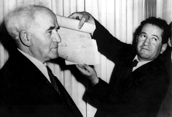 An official shows the signed document which proclaims the establishment of the new Jewish state of Israel declared by Prime Minister David Ben-Gurion, left, in Tel Aviv at midnight on May 14, 1948.  The Jews declared independence in the new state of Israel as the 25-year British mandate over Palestine ends.  (AP Photo)