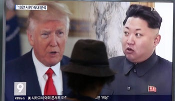 FILE - In this Aug. 10, 2017, file photo, a man watches a television screen showing U.S. President Donald Trump, left, and North Korean leader Kim Jong Un during a news program at the Seoul Train Station in Seoul, South Korea.
