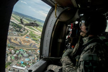 A helicopter carrying Joint Chiefs Chairman Gen. Joseph Dunford and United States Forces Korea Commander Gen. Vincent Brooks, left, takes a familiarization flight, Sunday, Aug. 13, 2017, near Pyeongtaek, South Korea.