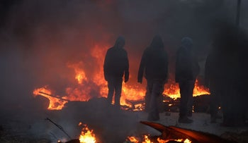 Youths burn tires at illegal outpost of Amona ahead of evacuation, February 1, 2017.