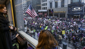 File photo: People watch as demonstrators march against Donald Trump.