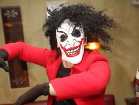 Witch, Purim costume: Person with thick mane of curly black hair wearing a witch whole-face mask, with black circles around the eyeholes, a painted nose and cheek contours and a broad red-[ainted grinning mouth.