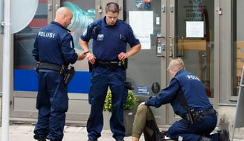 A video grab taken from Instagram on August 18, 2017 shows officials standing in a street next to a person lying on the ground in Turku where several people were stabbed.