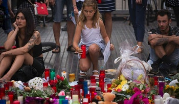 A girl places a candle after a terror attack that killed 14 people and wounded over 120 in Barcelona, Spain, Sunday, Aug. 20, 2017.