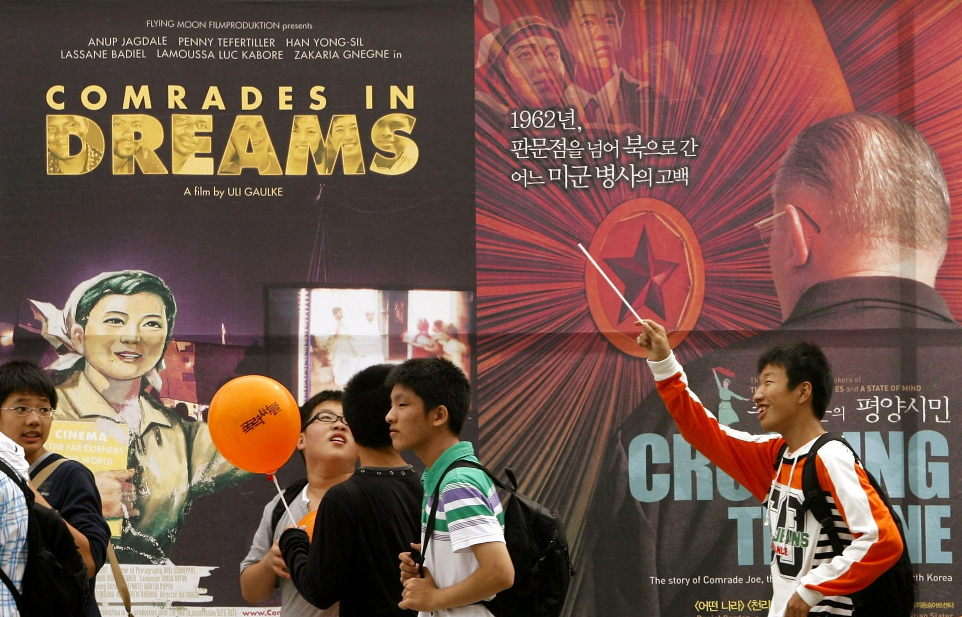 "Boys walk beside the posters of movies ""Comrades in Dreams"" and ""Crossing the Line"" at the 11th Busan International Film Festival in Busan, South Korea"