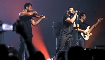 Hamed Sinno (C), the lead singer of Lebanese alternative rock band Mashrou' Leila performs with his band during a concert in Beirut, Lebanon, August 6, 2015