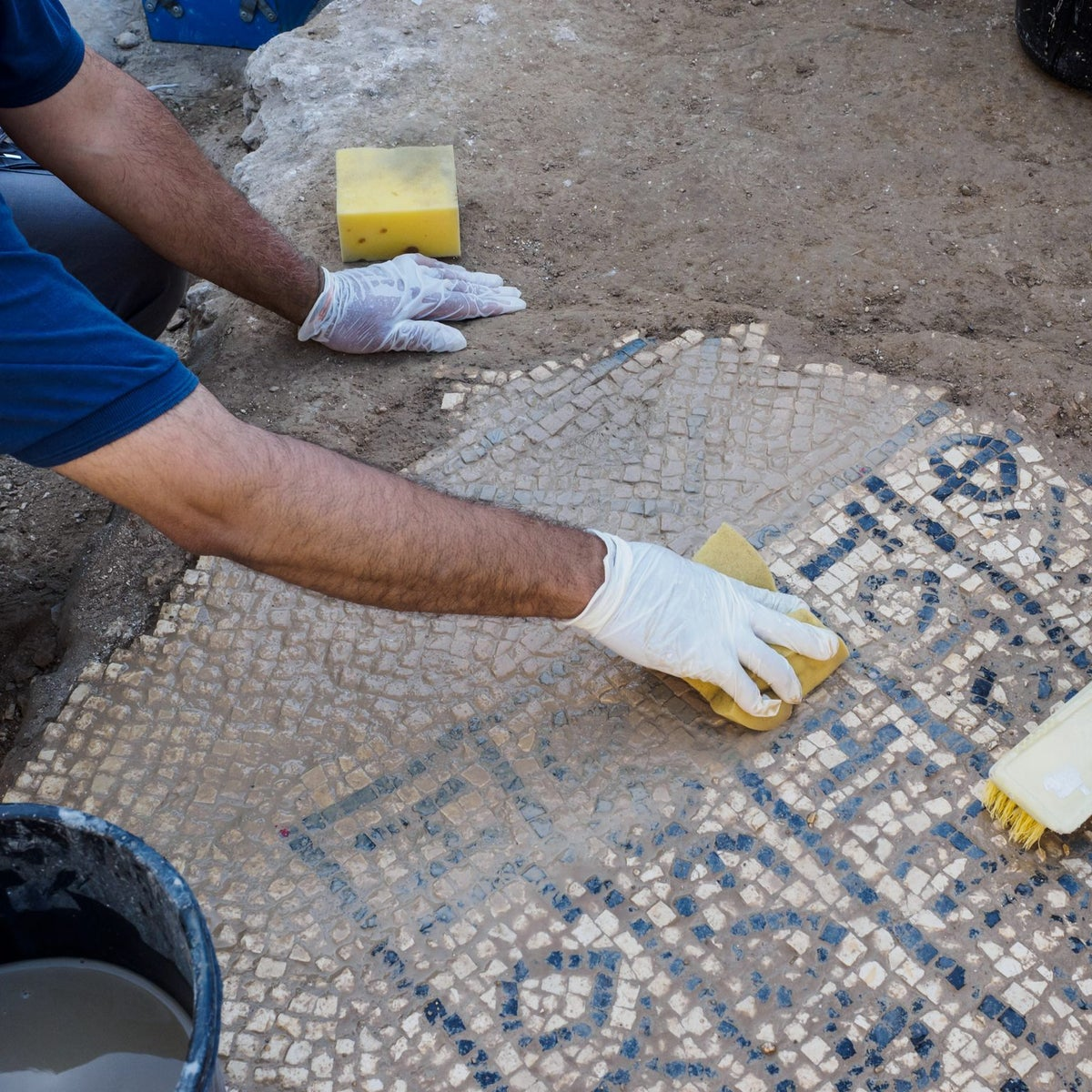 Cleaning the mosaic found in what seems to be a pilgrim's hotel in Jerusalem. The mosaic mentions both the Emperor Justinian and Abbot Constantine