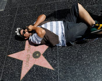 A person posing on the star of Donald Trump on the Hollywood Walk of Fame in Los Angeles, California, July 10, 2017.