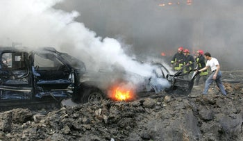 This file photo taken on February 14, 2005 shows firemen trying to extinguish the fire engulfing one of the cars of the convoy of former Lebanese prime minister Rafiq Hariri at the scene of a massive explosion in Beirut