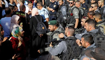 A Palestinian woman argues with an Israeli Border Police at the entrance to the compound known to Muslims as Noble Sanctuary and to Jews as Temple Mount, in Jerusalem's Old City, July 16, 2017.