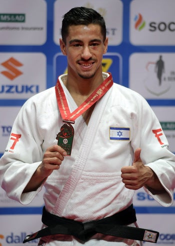 Bronze medalist of the men's -66kg category Israel's Tal Flicker celebrates on the podium during the medal ceremony at the World Judo Championships in Budapest on August 29, 2017.