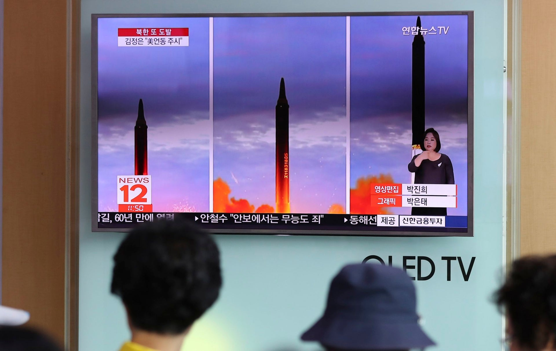 People watch a TV screen showing a local news program reporting about North Korea's missile launch at Seoul Train Station in Seoul, South Korea, Aug. 30, 2017.