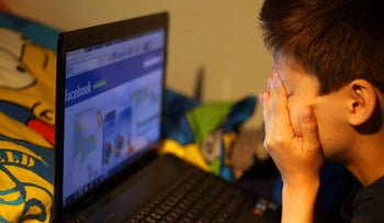 File photo: A boy looking at Facebook