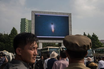 """A screen shows news coverage of an August 29 missile test launch in a public square outside a train station in Pyongyang on August 30, 2017.  North Korea leader Kim Jong-Un has promised more missile flights over Japan, insisting his nuclear-armed nation's provocative launch was a mere """"curtain-raiser"""", in the face of UN condemnation and US warnings of severe repercussions. / AFP PHOTO / KIM Won-Jin"""