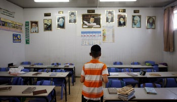 A boy places books on classroom tables before a lesson at Moaz Hatorah, an all-boys school, in the ultra-Orthodox Jewish community of Bnei Brak, near Tel Aviv, Israel July 12, 2017. Picture taken July 12, 2017. REUTERS/Nir Elias