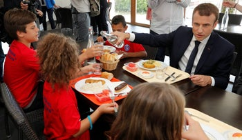 French President Emmanuel Macron shares a lunch with children as he visits a recreational center for children in Moisson, France, August 3, 2017.
