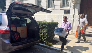 Workers carry boxes out of the Russian consulate in San Francisco as acrid, black smoke was seen pouring from a chimney at the stately building in a historic area of the city Friday September 1, 2017.
