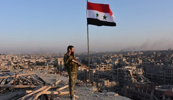 FILE PHOTO: Syrian pro-government forces stand on top of a building overlooking Aleppo in the city's Bustan al-Basha neighbourhood on November 28, 2016, during their assault to retake the entire northern city from rebel fighters.