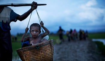 An ethnic Rohingya child from Myanmar is carried in a basket past rice fields after crossing over to the Bangladesh side of the border, Sept. 1, 2017