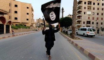 File photo: ISIS member waves an ISIS flag in Raqqa, Syria on June 29 2014.