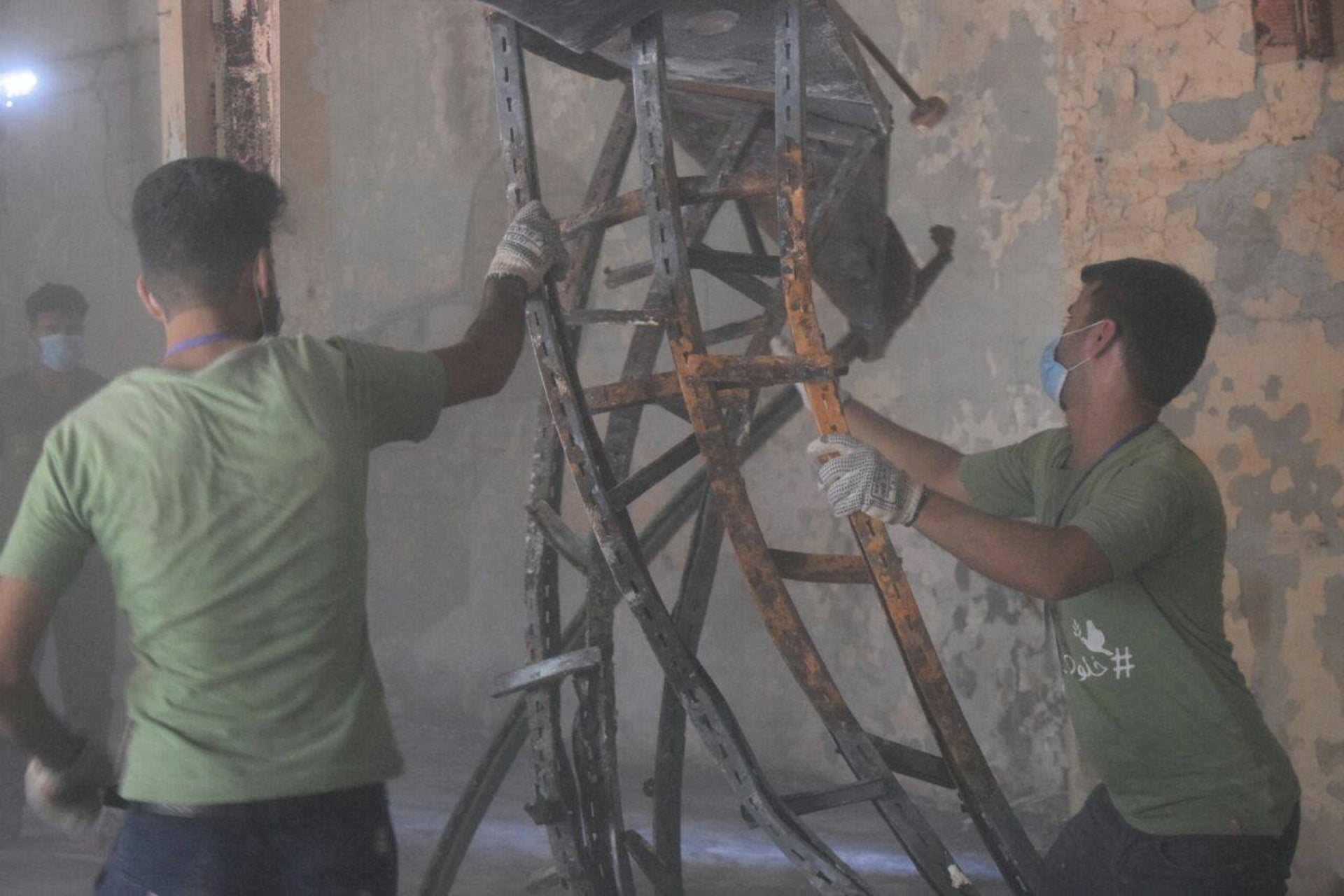 Students are removing a burned books stand at Mosul's library. They discovered that not everything went up in flames.