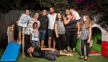 Racheli (striped shirt), Sigal (holding a child second to right) and their eight children, including Matan (held by Racheli)