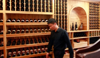 A man walks past bottles of wine on display at the Winston Wines Pty store in Shanghai, China, on Tuesday, Oct. 18, 2011.
