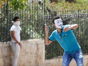 Palestinians hurl stones towards Israeli soldiers during clashes in the West Bank city of Bethlehem, Friday, July 28, 2017.