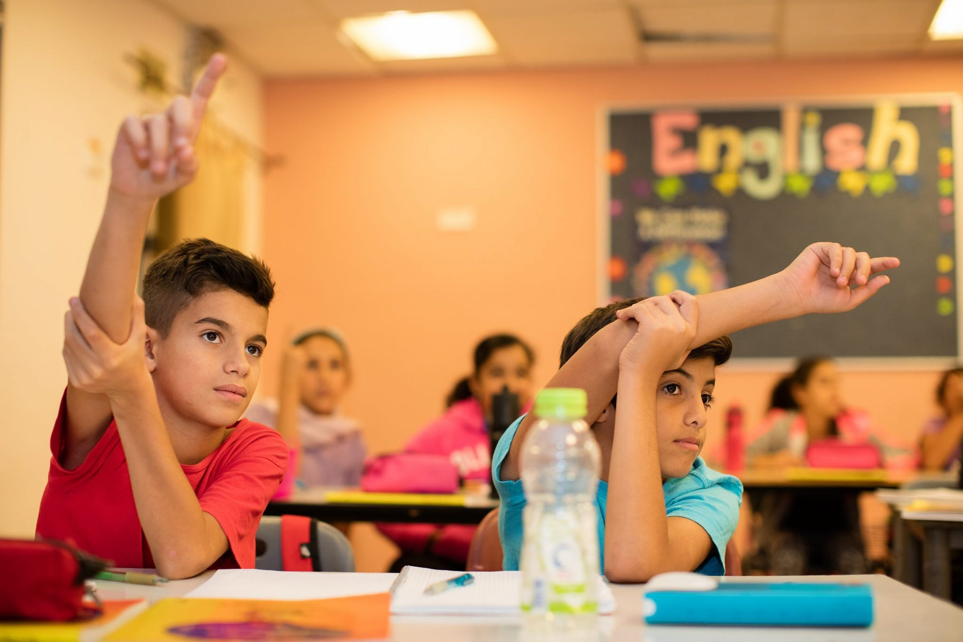 Students raise their hand in a classroom at the Hand in Hand bilingual school in Jerusalem.