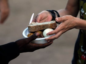 An African migrant receives food from a volunteer at Levinsky park in South Tel Aviv June 6, 2012. About 60,000 Africans have crossed into Israel across its porous border with Egypt in recent years. Israel says the vast majority are job seekers, disputing arguments by humanitarian agencies that they should be considered for asylum. Picture taken June 6, 2012. REUTERS/Baz Ratner