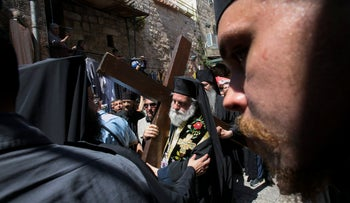 An Orthodox worshipper carry a cross near the Church of the Holy Sepulchre during the Eastern Church's Good Friday procession in the Old City of Jerusalem