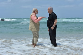 Indian Prime Minister Narendra Modi and Prime Minister Benjamin Netanyahu stand in the Mediterranean Sea on their visit to a mobile desalination unit on July 6, 2017.