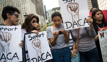 """""""Dreamers"""" originally from Ecuador watch Attorney General Jeff Sessions' remarks on ending the DACA program on a smartphone in Manhattan, September 5, 2017."""