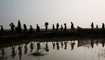 Members of Myanmar's Rohingya ethnic minority walk through rice fields after crossing the border into Bangladesh near Cox's Bazar's Teknaf area, Tuesday, Sept. 5, 2017.