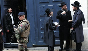 A French soldier patrols next to a Jewish school, in Paris, Tuesday, Jan. 13, 2015.