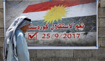"A man passes by a banner that reads ""Yes for the independence of Kurdistan"" in Kirkuk, Iraq, September 10, 2017."