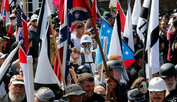 In this Saturday August 12, 2017 file photo, white nationalist demonstrators walk into the entrance of Lee Park surrounded by counter demonstrators in Charlottesville, Virginia.