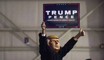 An attendee, wearing a Donald Trump mask, holds up a campaign sign at a campaign rally for Donald Trump, 2016 Republican presidential nominee, in Moon Township, Pennsylvania, U.S., on Sunday, Nov. 6, 2016. Trump and his aides insist his supporters' enthusiasm will give him an edge in Tuesday's national election. Photographer: Ty Wright/Bloomberg