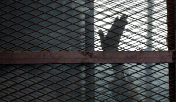 A Muslim Brotherhood member gestures from a defendants cage in a courtroom in Torah prison, southern Cairo, Egypt.