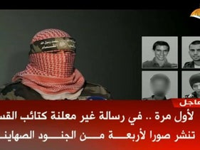Hamas militant with images of Lt. Hadar Goldin, St.-Sgt. Oron Shaul, Avera Mengistu and Hisham al-Sayyad.
