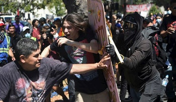 In this Sunday, Aug. 27, 2017, file photo, demonstrators clash during a free speech rally, in Berkeley, Calif. Police in the city of Berkeley can use pepper spray on violent demonstrators after the City Council voted Tuesday, Sept. 12