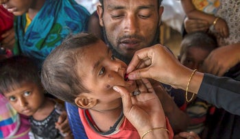 A Bangladeshi health worker administers vaccine to a Rohingya Muslim boy, who crossed over from Myanmar into Bangladesh, at Balukhali refugee camp, Bangladesh, Sunday, Sept. 17, 2017